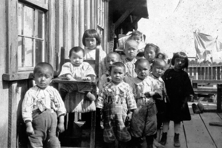 Children belonging to a cannery gather at a Japanese cabin